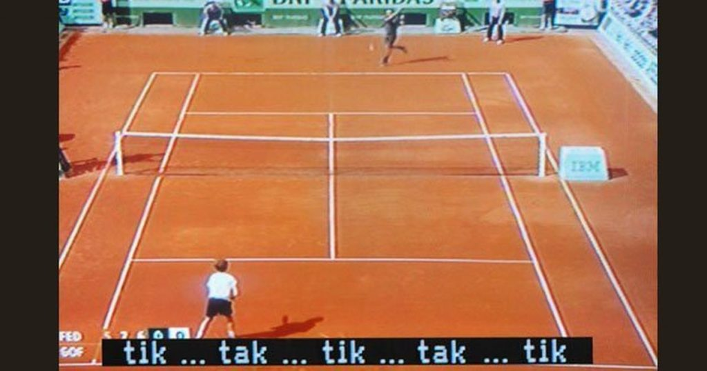Long shot of TV coverage of tennis match, captioned [tik...tak...tik...tak...]