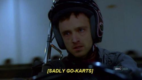 "Young man wearing a helmet holds a vehicle's steering wheel, visibly crying with red and tear-filled eyes. Captio reads: ""[SADLY GO-KARTS]'"