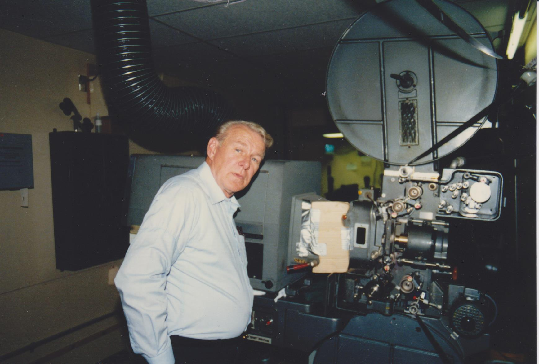 Older man turning towards the camera, standing next to projection equipment in a dimly lit booth.