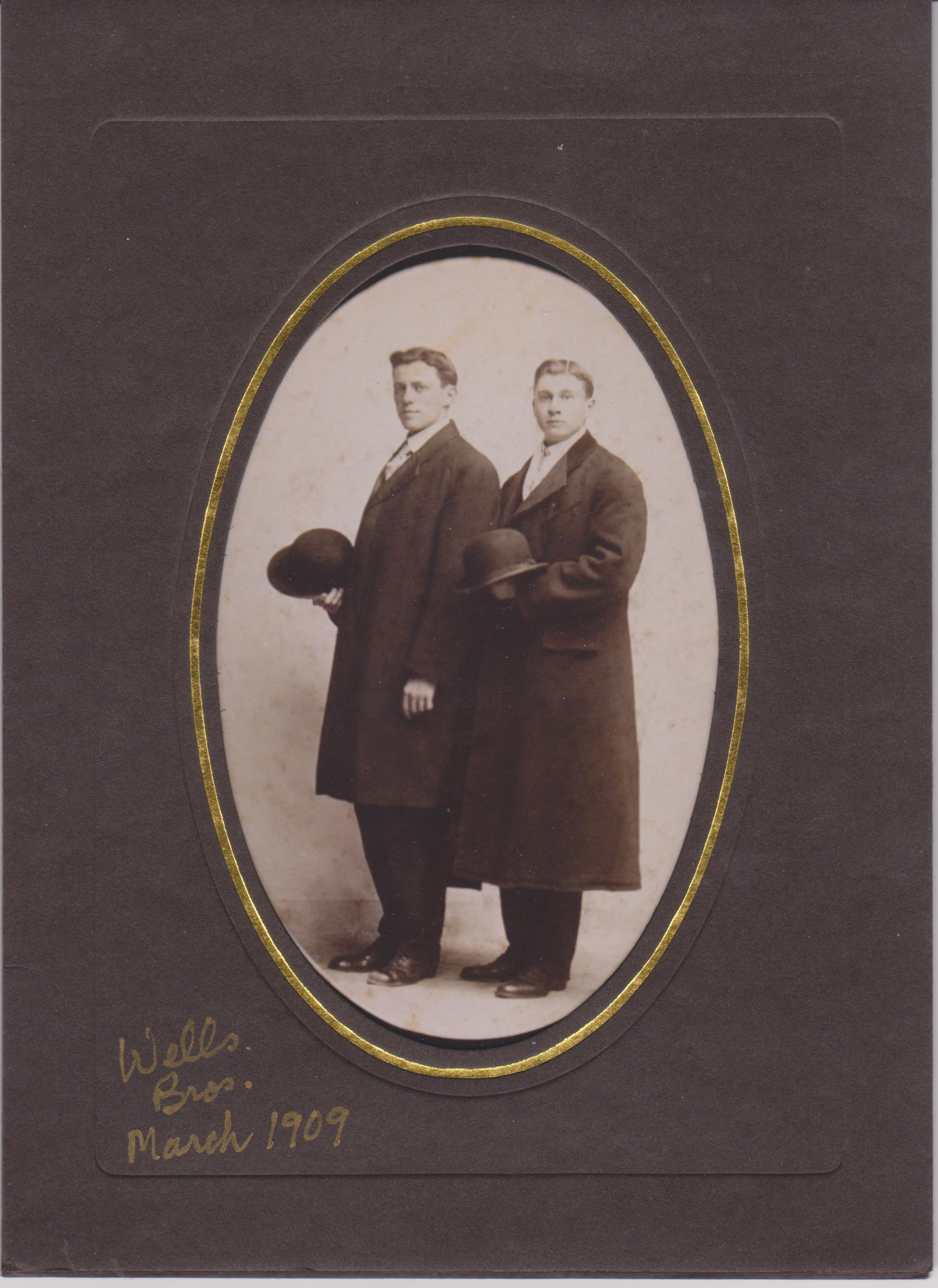 "Framed sepia full length portrait photograph, annotated with ""Wells Bros. March 1909"" showing two twentyish men in great coats, holding their hats, with serious demeanours"