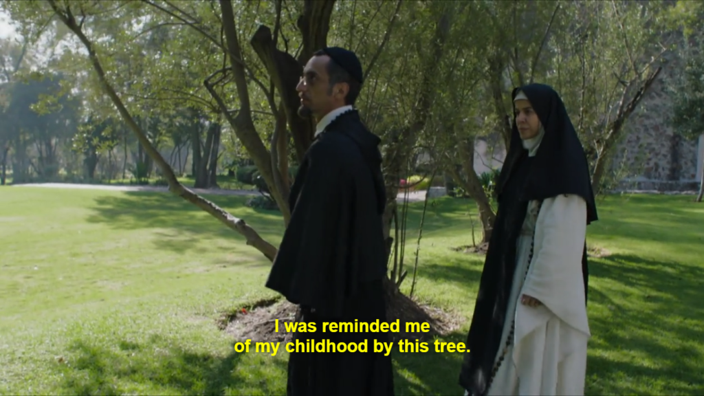 """Three quarter shot of a priest (left) and nun (right) walking in the shade by a tree in a bright, cared for garden. They are both in very conservative, concealing and strictly black and white clothing. Caption reads: """"I was reminded me of my childhood by this tree."""""""