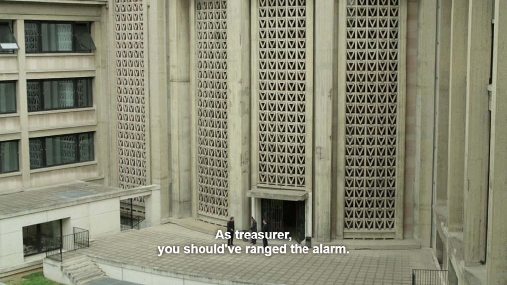 Very long shot with three men in suits speaking just outside the door of an enormous white cement building, the architecture is modernist, vertical and imposing in atmosphere.
