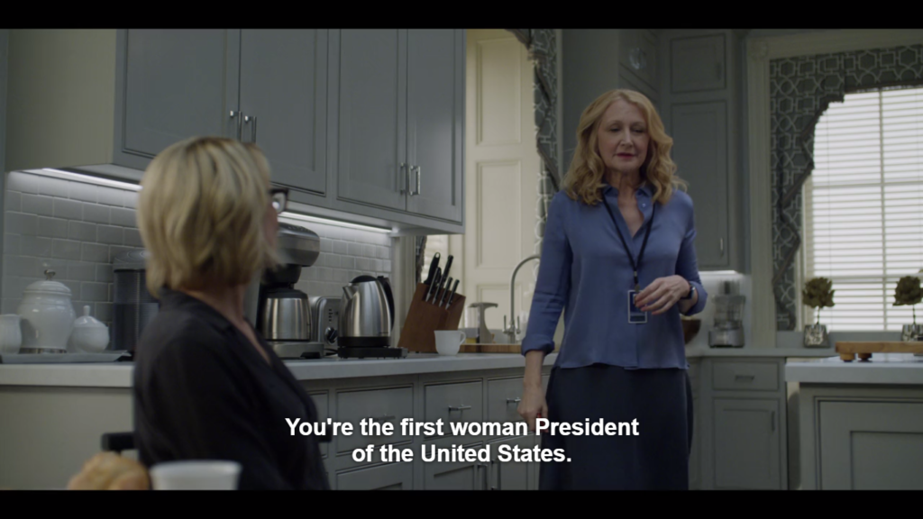 """A woman stands in a well-appointed kitchen and another sits in front of her facing away from the camera. Caption reads: """"You're the first woman President of the United States."""""""