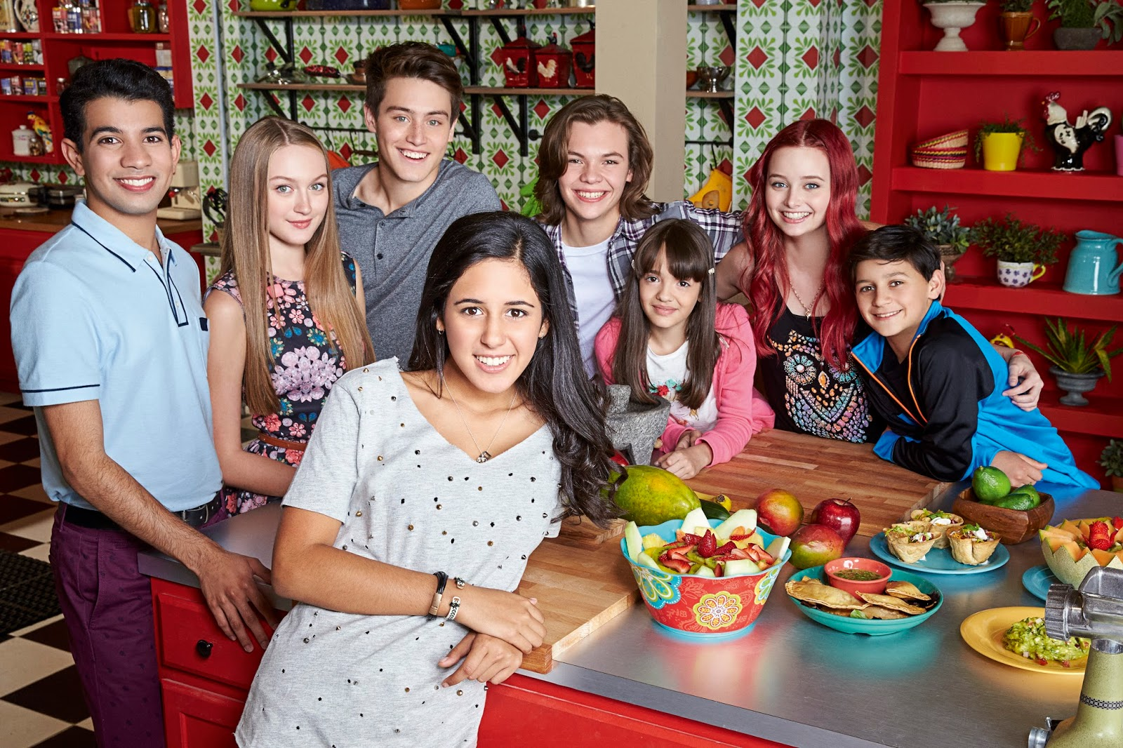 A group of 8 youth between the ages of 8 and 16, gathered around a commercial kitchen prep table laden with food; facing and smiling at the camera