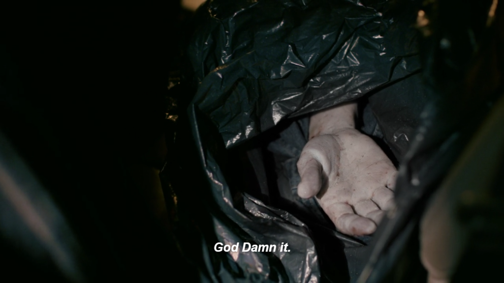 """Close-up shot of a human hand sticking out of a dark green garbage bag. Caption reads: """" God Damn it."""""""