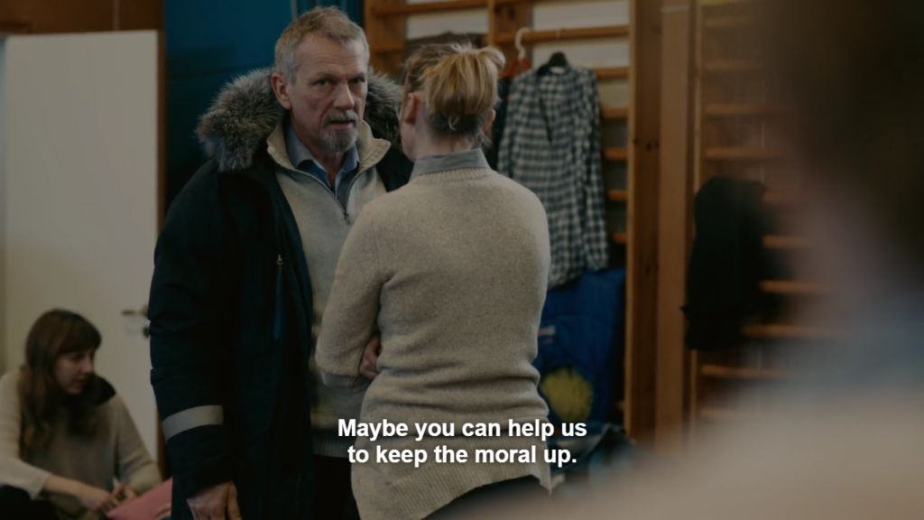 """A middle-aged man wearing a sweater and parka faces the camera, speaking to a woman whose back is visible, wearing a beige sweater and ponytail, in a gym as indicated by climbing bars. Caption reads: """"Maybe you can help us to keep the moral up."""""""
