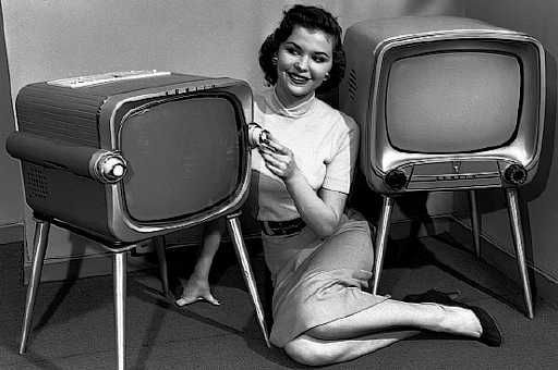Black and white photo from the 1950s with a young woman seated on the carpet between two television sets; image appears to be an advertisement