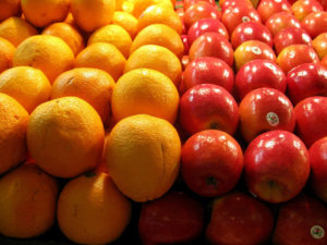 Colour photo of oranges in vertical rows on the left and red applies on the right, as they might be lined up on display in a grocery store.