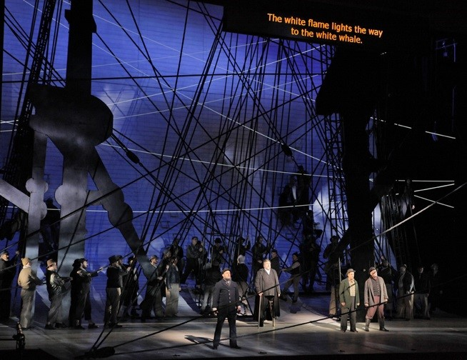 Long shot colour photo of an opera production with a seafaring theme as a set and English surtitles projected above the stage