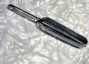 Old-fashioned vegetable or fruit peeler, with bare metal handle, against a mottled grey background