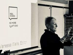 Author at Mohawk College, Accessible Media Program, shown in front of a screen with her logo for Reel Words projected, with the slogan No More Craptions!, and Vanessa Wells, Editor at the bottom. Black and white photo with screen at left, Vanessa at right, gesturing while speaking.