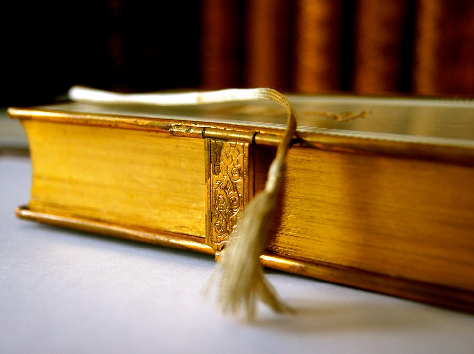 Colour photo closeup of gilded Bible pages, with gold cover, snap closure and tasselled bookbark hanging in the foreground.