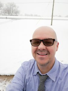 Head shot of Dr. Sean Zdenek in a blue shirt, dark glasses, outside with snow behind him; he is smiling broadly