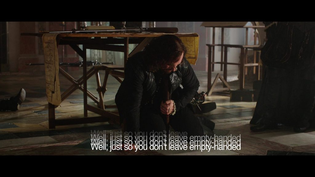Video clip of a musketeer collapsed on the floor with a caption that says, Well, just so you don't leave empty-handed, with the text repeated 3 times and overlapping, reflecting his experience of being poisoned