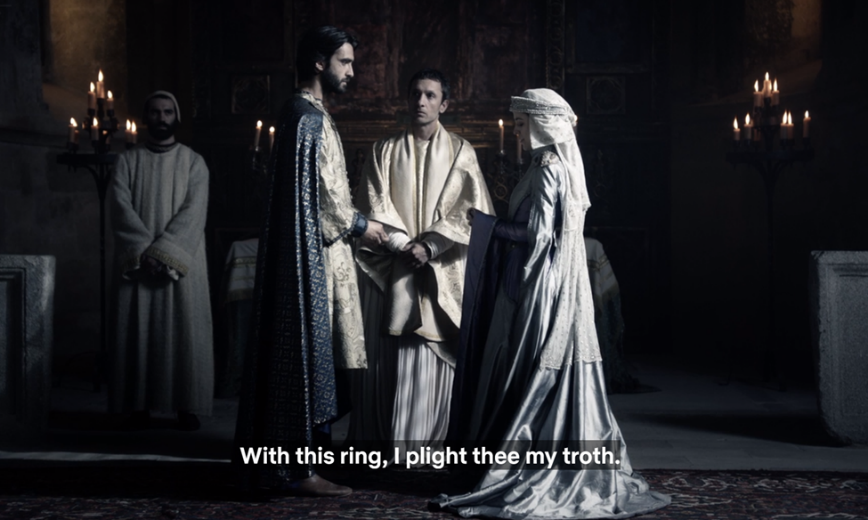 "Video still of medieval characters, a priest flanked by a man and woman facing each other in a church, captioned ""With this ring, I plight thee my troth."""