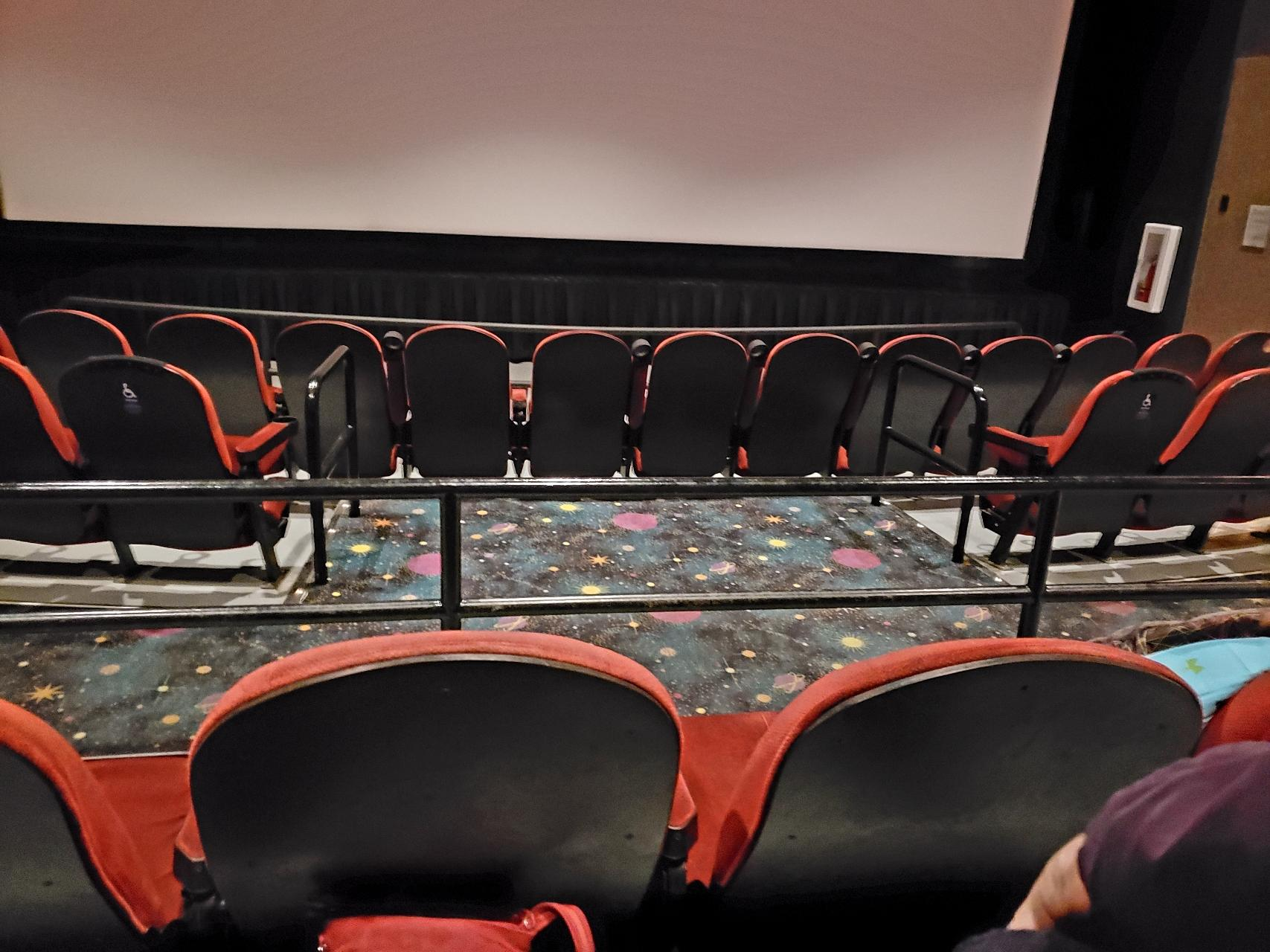"Shot taken from cinema seating of a section before it that is ostensibly reserved for ""accessible seating"": there is an area of four seats' width barred off at the sides from the other seats in the middle of the row. This section is in the second row of the cinema, with a transverse aisle behind it."