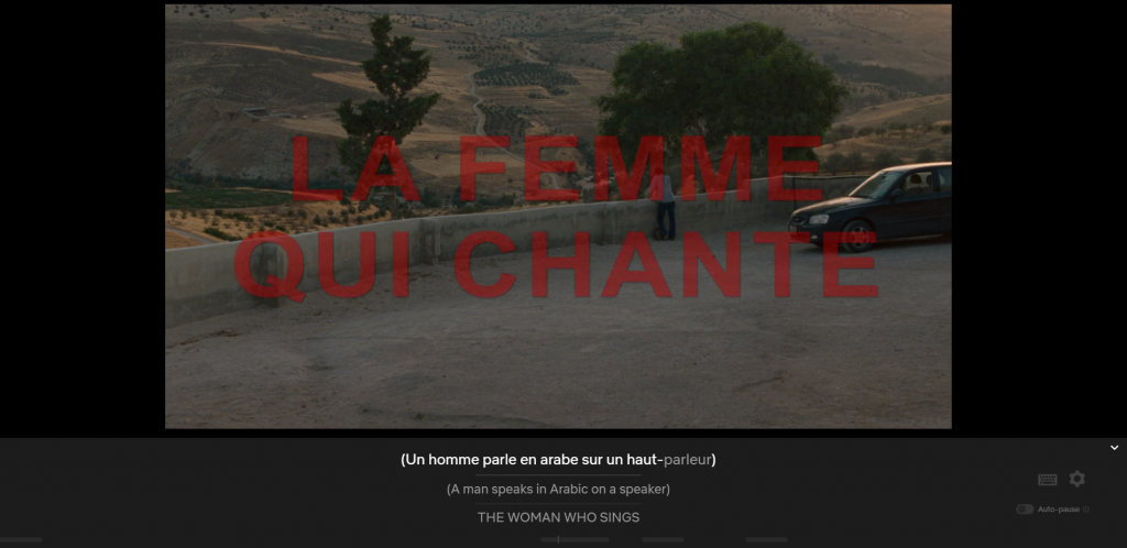 Vista with woman at wall and car in midground, chapter title La Femme Qui Chante, captioned Un homme parle en arabe sur un haut-parleur/A man speakes in Arabic on a speaker/THE WOMAN WHO SINGS