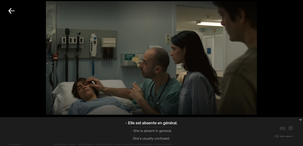 Doctor examining woman in hospital, adult children looking on, captioned Elle est absente en general/She is absent in general/She's usually confused