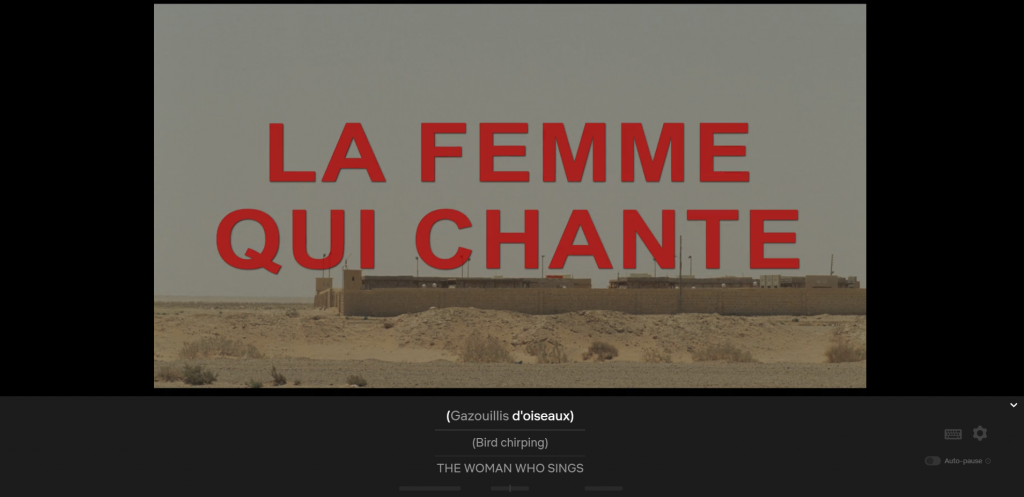 Vista with woman at wall and car in midground, chapter title La Femme Qui Chante, captioned Gazouillis d'oiseaux/Bird chirping/THE WOMAN WHO SINGS