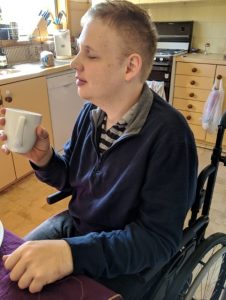 Torso shot of Jonathan Craig in his wheelchair at a table, coffee cup in hand.