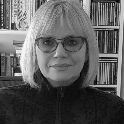 Black and white headshot of Gaele, before a bookshelf. She has chin-length blond hair and glasses and is wearing a dark turtleneck