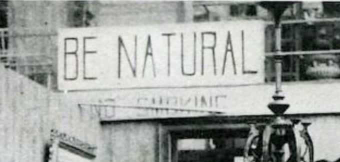 Old black and white photo of a sign on wall inside an industrial space that says BE NATURAL.